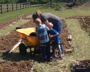 Amy Gardner and sons helping plant permaculture garden; photo by Kari Lygren